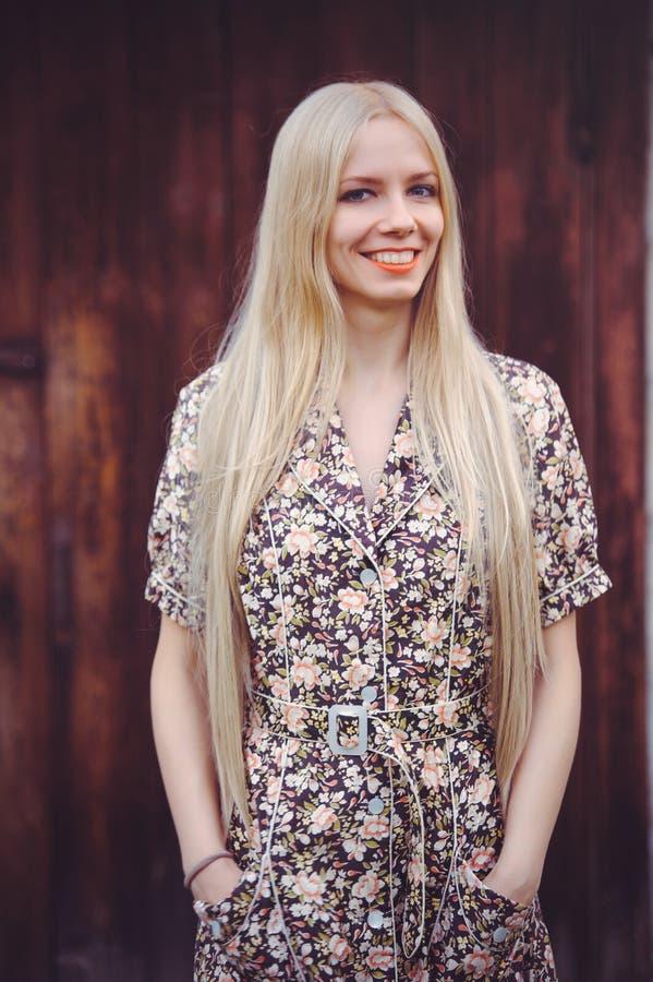 De mooie jonge vrouw doted binnen de zomerkleding op rode oude houten achtergrond, bekijkend camera rustieke stijl, vrij stock fotografie