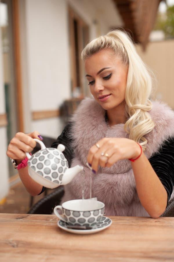 De mooie jonge vrouw drinkt thee op bar terace in de vroege herfst royalty-vrije stock foto
