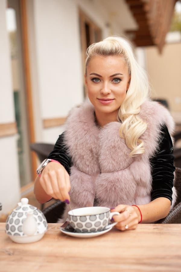 De mooie jonge vrouw drinkt thee op bar terace in de vroege herfst stock foto's