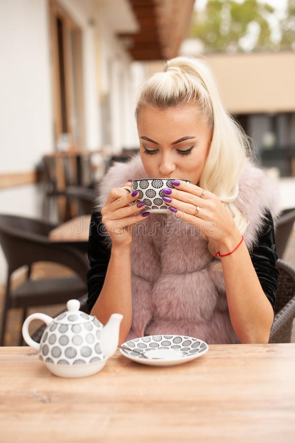 De mooie jonge vrouw drinkt thee op bar terace in de vroege herfst stock fotografie