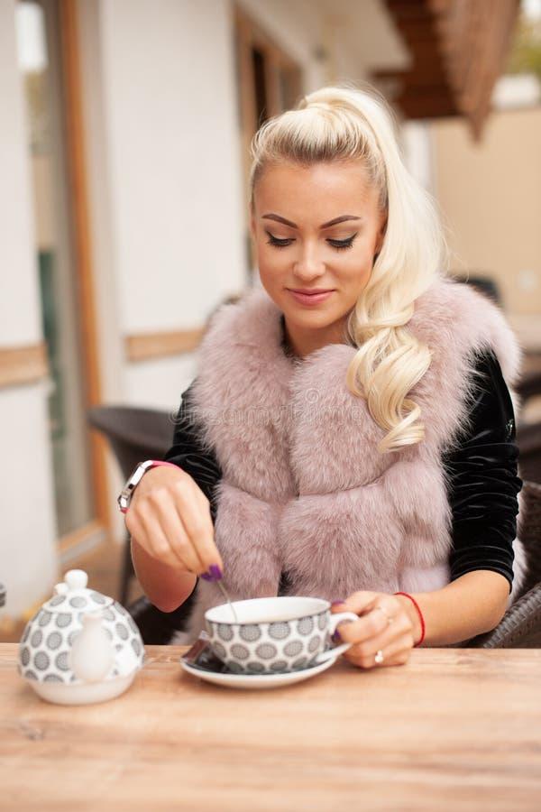 De mooie jonge vrouw drinkt thee op bar terace in de vroege herfst stock foto
