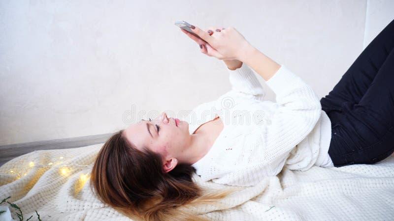 De mooie Jonge Vrouw drukt bericht op mobiel, terug liggend op op pl stock afbeelding
