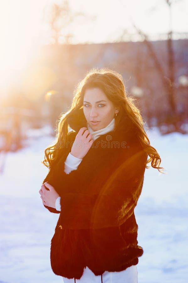De mooie jonge vrouw in een bontjas loopt in de de winterstraat stock afbeeldingen