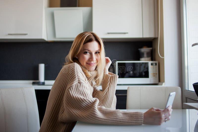 De mooie jonge vrouw in een comfortabele sweater zit in de keuken gebruikend een videogesprek in de boodschapper royalty-vrije stock fotografie