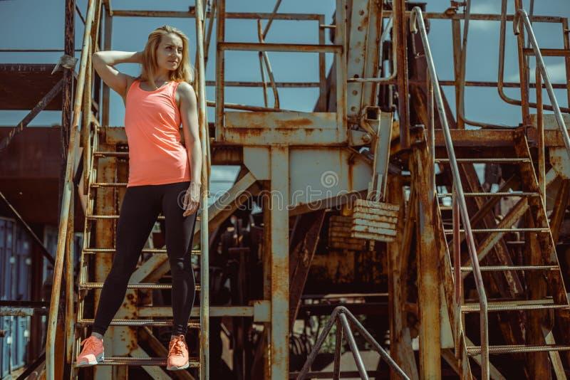 De mooie jonge vrouw in een oranje T-shirt bevindt zich op roestige stappen royalty-vrije stock afbeelding
