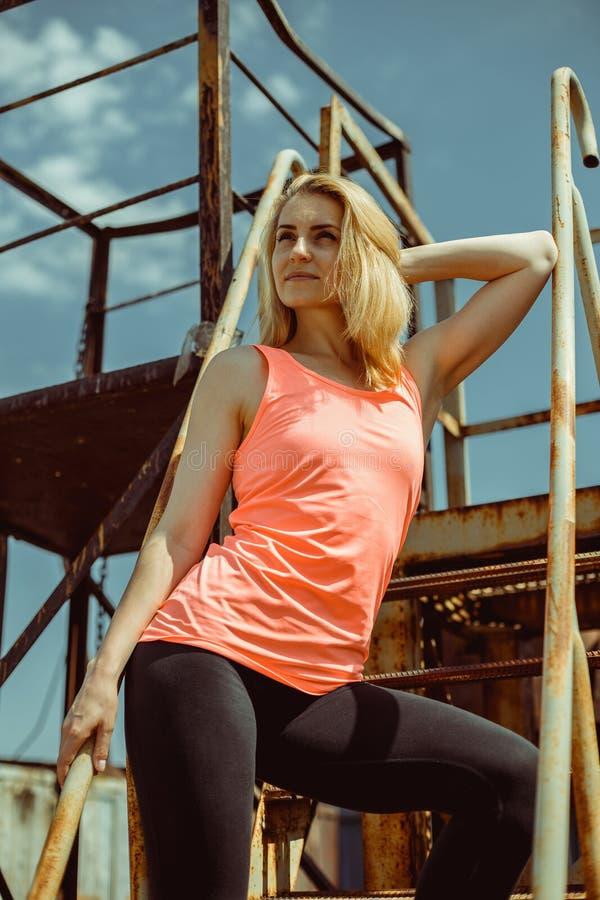 De mooie jonge vrouw in een oranje T-shirt bevindt zich op roestige stappen royalty-vrije stock fotografie