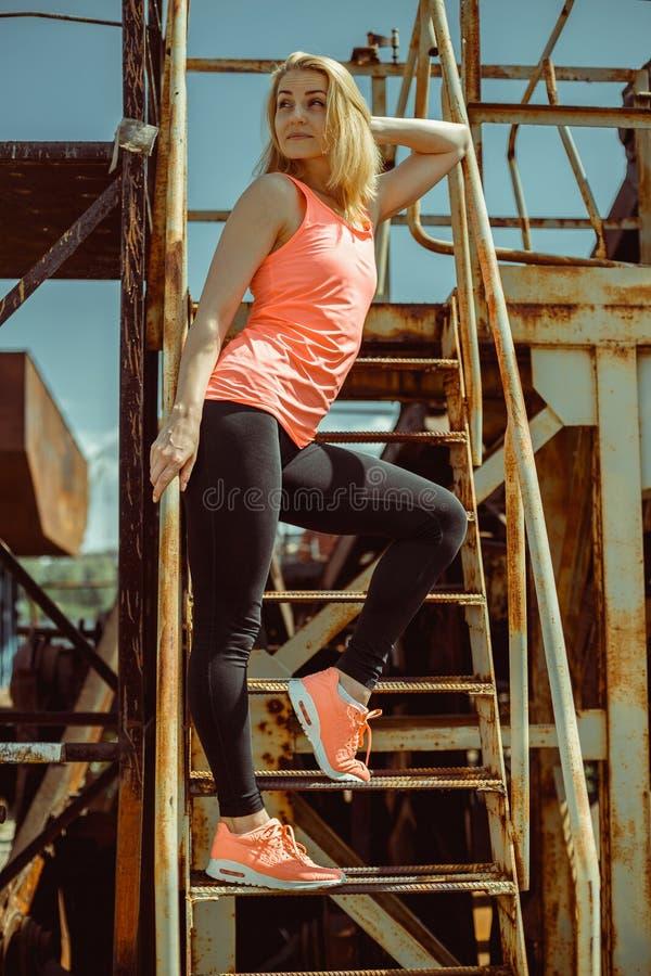 De mooie jonge vrouw in een oranje T-shirt bevindt zich op roestige stappen stock afbeelding