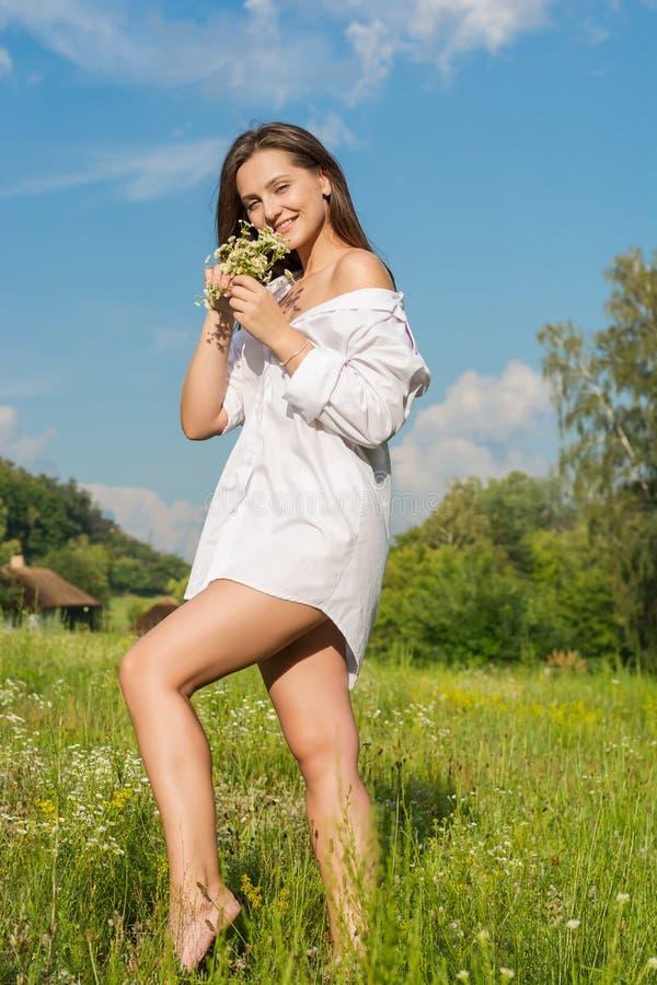 De mooie jonge vrouw in een wit overhemd houdt wilde bloemen a royalty-vrije stock afbeeldingen
