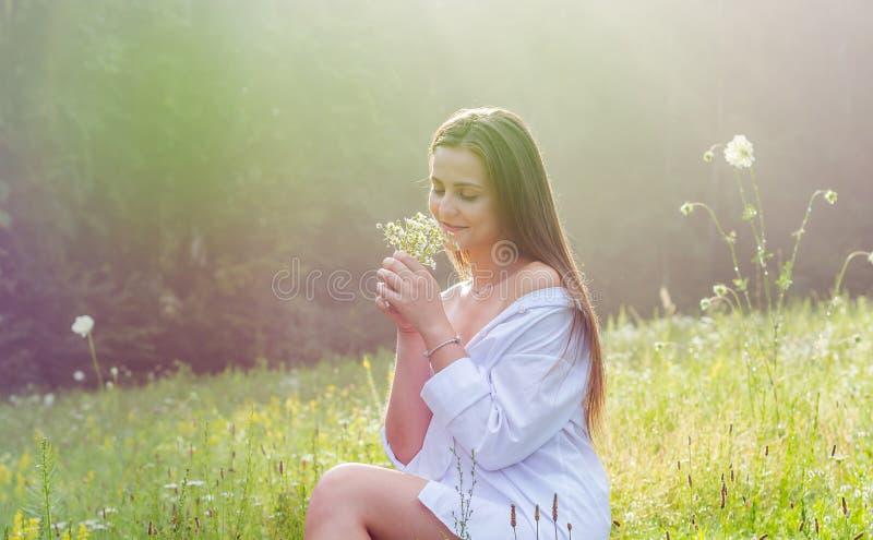 De mooie jonge vrouw in een wit overhemd houdt wilde bloemen i royalty-vrije stock foto