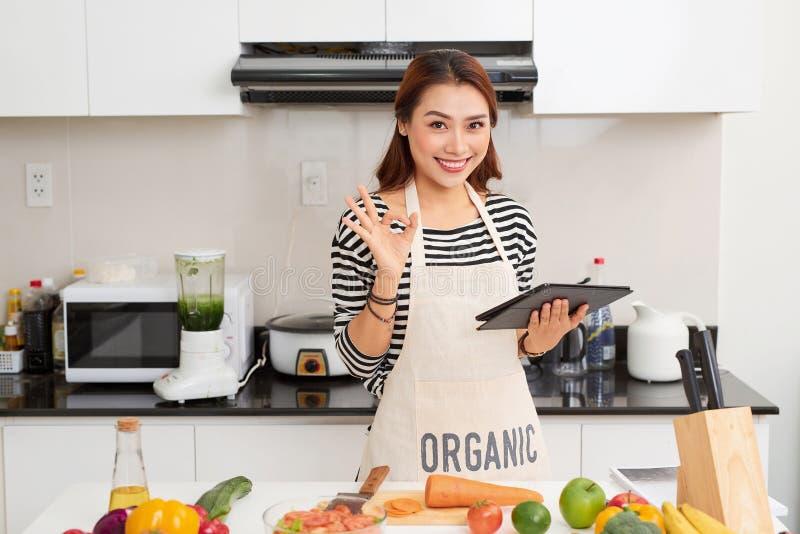 De mooie jonge vrouw gebruikt een digitale tablet en glimlacht terwijl thuis het koken in keuken stock foto's