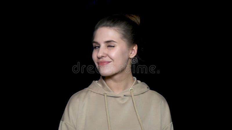 De mooie jonge vrouw geeft flirty glimlach en knipoogt Portret van vrolijke flirtdame die beige sweatshirt draagt stock foto's