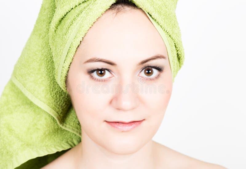 De mooie Jonge vrouw gekleed in een badhanddoek maakt een kosmetisch masker op het gezicht de schoonheidsindustrie en de zorg van royalty-vrije stock afbeelding