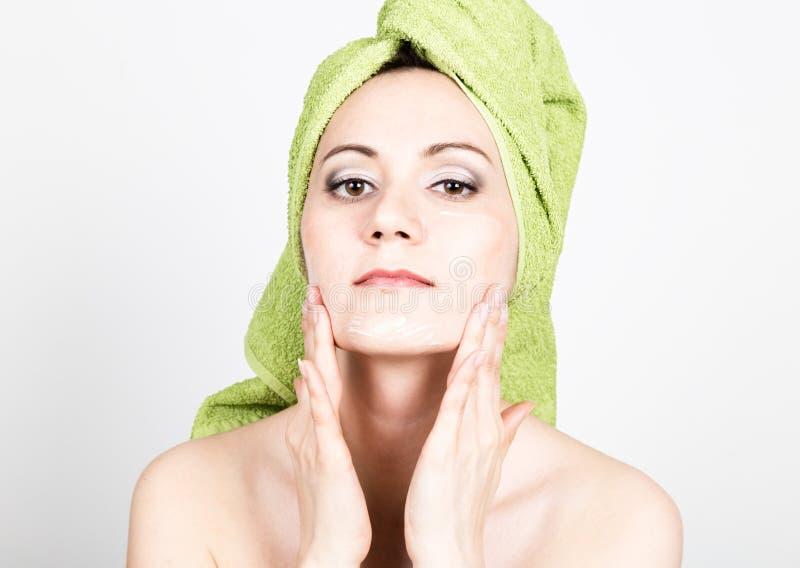 De mooie Jonge vrouw gekleed in een badhanddoek maakt een kosmetisch masker op het gezicht de schoonheidsindustrie en de zorg van royalty-vrije stock afbeeldingen