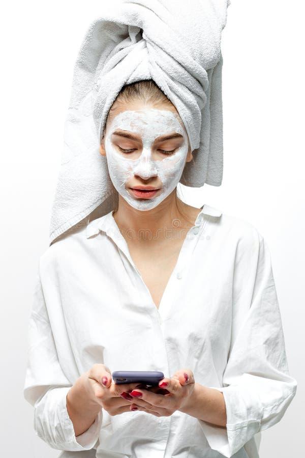 De mooie jonge vrouw gekleed in witte kleren met een witte handdoek op haar haar en kosmetisch masker op haar gezicht houdt mobie royalty-vrije stock afbeelding