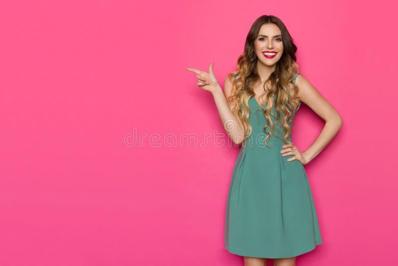 De mooie Jonge Vrouw in Groene Kleding richt op het Roze Exemplaar Ruimte en Glimlachen stock foto's