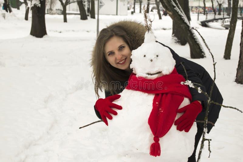 De mooie jonge vrouw het blonde met blauwe ogen omhelst een sneeuwman royalty-vrije stock afbeeldingen