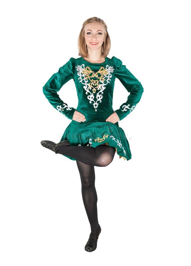 De mooie jonge vrouw in het Iers danst groene kleding springend isoleert stock fotografie