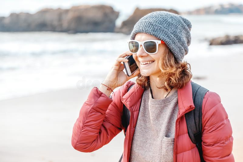 De mooie jonge vrouw in hoed en zonnebril spreekt door mobiele pho stock afbeeldingen