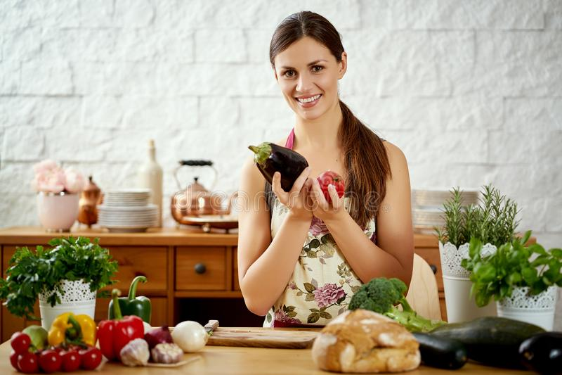 De mooie jonge vrouw houdt aubergine en tomaat in de keuken bij een lijsthoogtepunt van groenten royalty-vrije stock foto