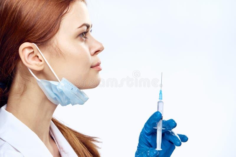 De mooie jonge vrouw houdt een spuit in medische kleren op wit geïsoleerde achtergrond, arts, portret royalty-vrije stock foto's