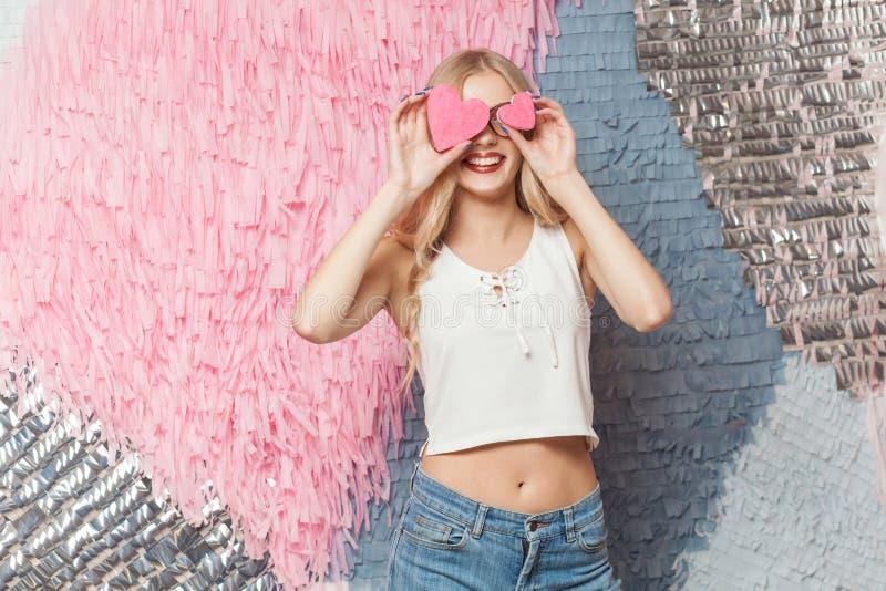 De mooie jonge vrouw, houdt twee koekjes in vorm van harten, havi royalty-vrije stock afbeelding
