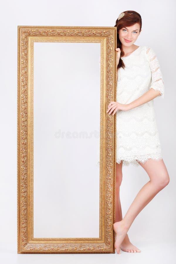 De mooie jonge vrouw in kleding bevindt zich dichtbij frame stock fotografie