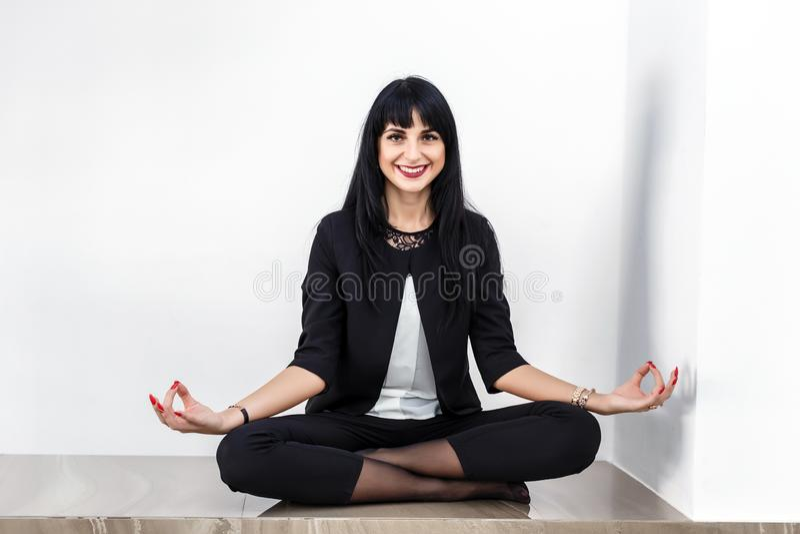 De mooie jonge vrouw kleedde zich in een zwarte pakzitting in lotusbloempositie inzake een vloer in bureau, het glimlachen, bekij royalty-vrije stock afbeelding