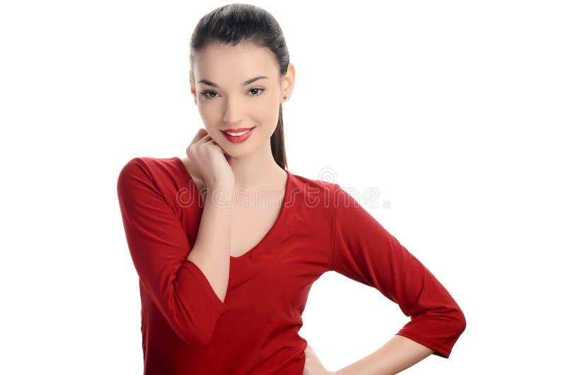De mooie jonge vrouw kleedde zich in rood met het sexy rode lippen glimlachen. royalty-vrije stock afbeeldingen