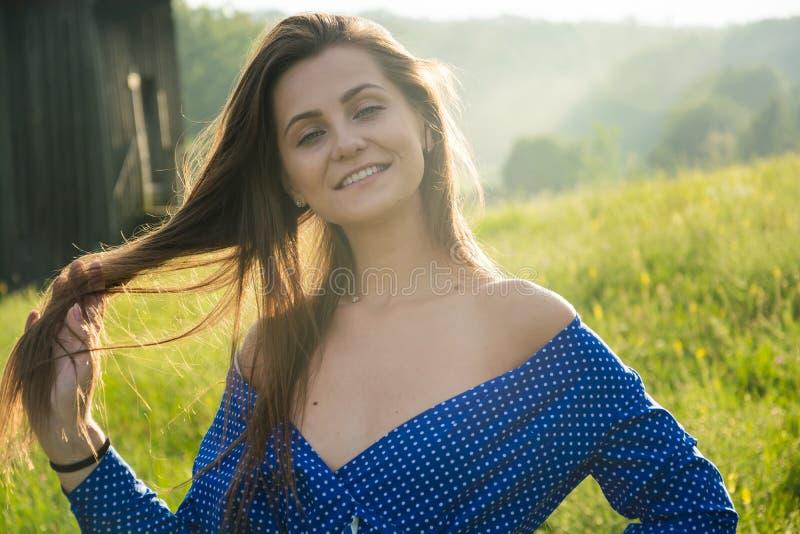 De mooie jonge vrouw lacht in het zonlicht op een weidewi stock afbeeldingen