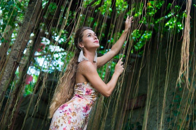 De mooie jonge vrouw leunt tegen een boom in het regenwoud die sexy kleding dragen royalty-vrije stock foto