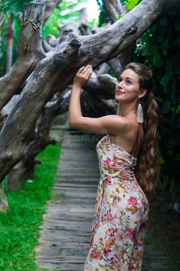 De mooie jonge vrouw leunt tegen een boom in het regenwoud die sexy kleding dragen stock foto's