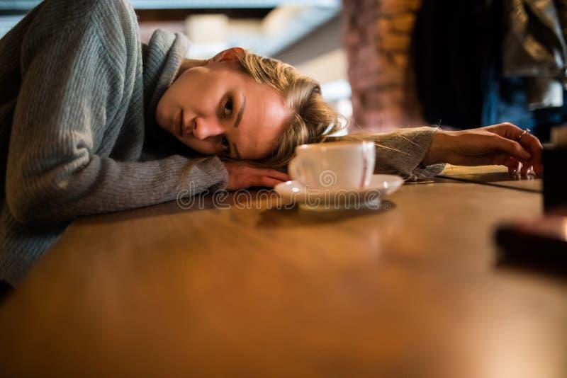 De mooie jonge vrouw ligt op handen, zit bij houten lijst in cafetaria, drinkt koffie Ontspan en rust concept royalty-vrije stock afbeeldingen