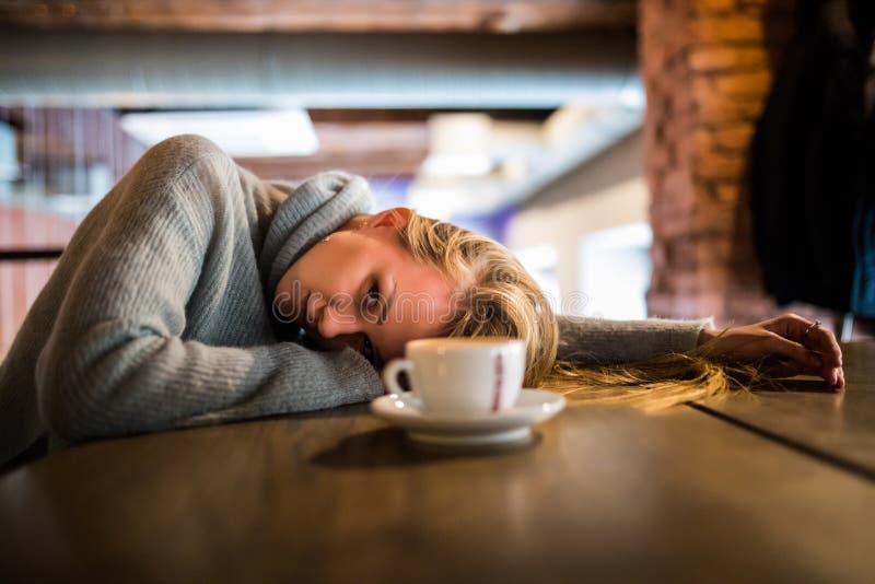 De mooie jonge vrouw ligt op handen, zit bij houten lijst in cafetaria, drinkt koffie Ontspan en rust concept stock fotografie