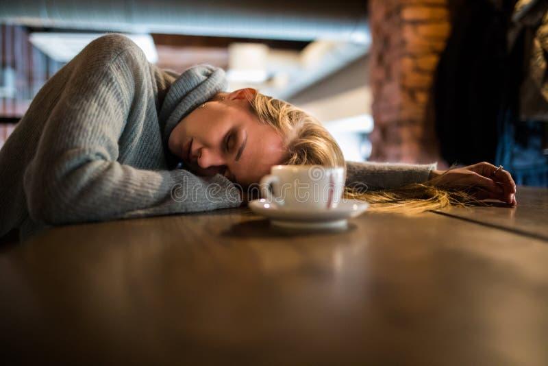 De mooie jonge vrouw ligt op handen, zit bij houten lijst in cafetaria, drinkt koffie Ontspan en rust concept royalty-vrije stock foto