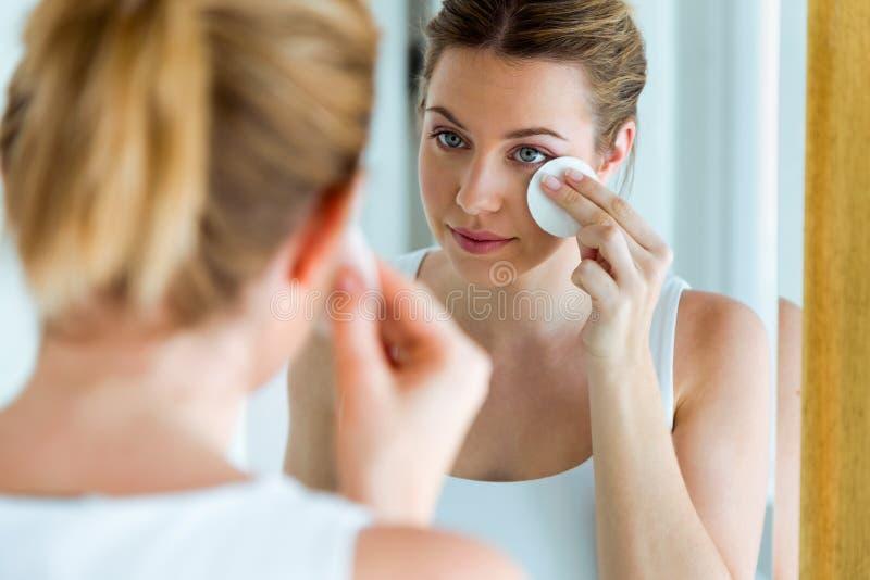 De mooie jonge vrouw maakt haar gezicht schoon terwijl het kijken in de badkamers royalty-vrije stock foto