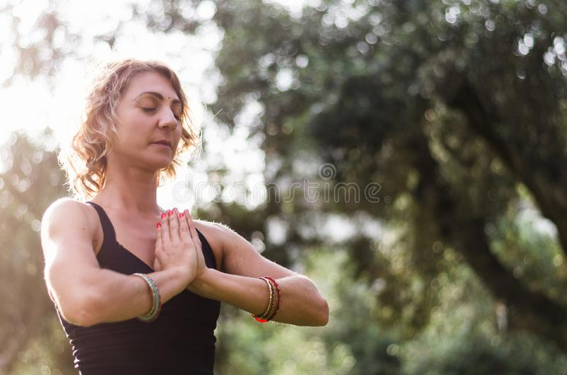 De mooie jonge vrouw mediteert in yogaasana Padmasana - Lotus stelt op het houten dek in het de herfstpark royalty-vrije stock afbeeldingen
