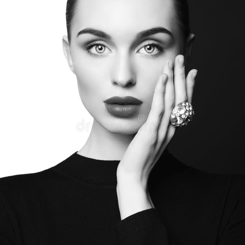 De mooie jonge vrouw met grote ring stelt in studio royalty-vrije stock afbeelding