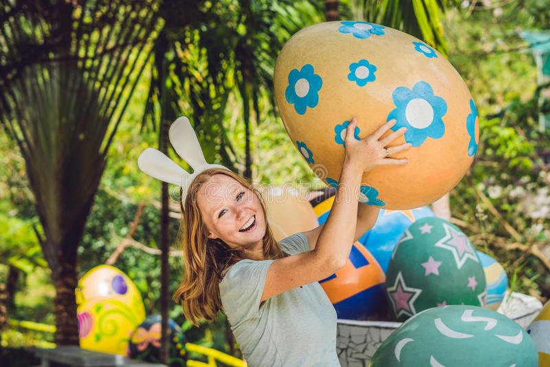 De mooie jonge vrouw met konijntjesoren die pret met traditionele paaseieren hebben jaagt, in openlucht Het vieren Pasen vakantie royalty-vrije stock fotografie