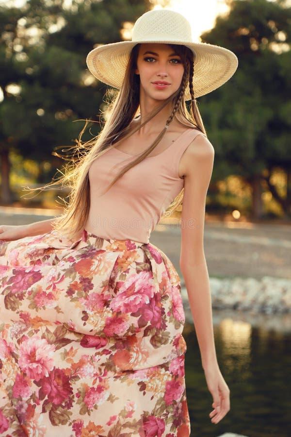 De mooie jonge vrouw met lang donker haar draagt elegante kleding en hoed stock foto