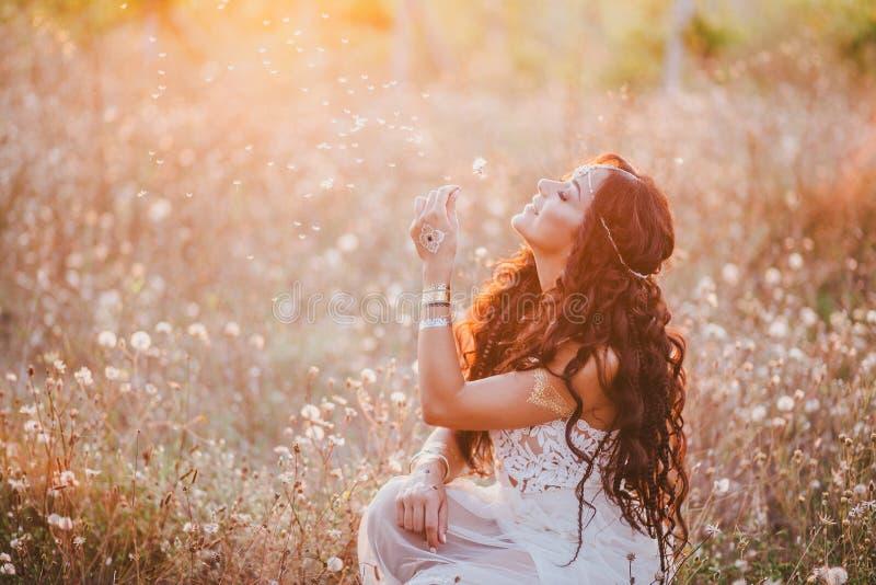 De mooie jonge vrouw met lang krullend haar kleedde zich in de kleding van de bohostijl het stellen op een gebied met paardebloem stock afbeeldingen