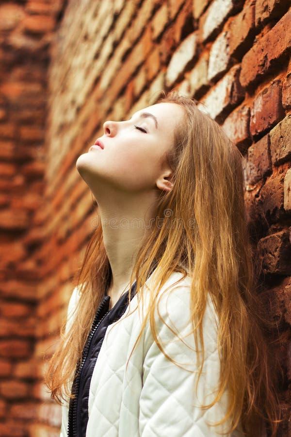 De mooie jonge vrouw met lang rood haar bevindt zich dichtbij rood Wall Street in de stad royalty-vrije stock afbeelding