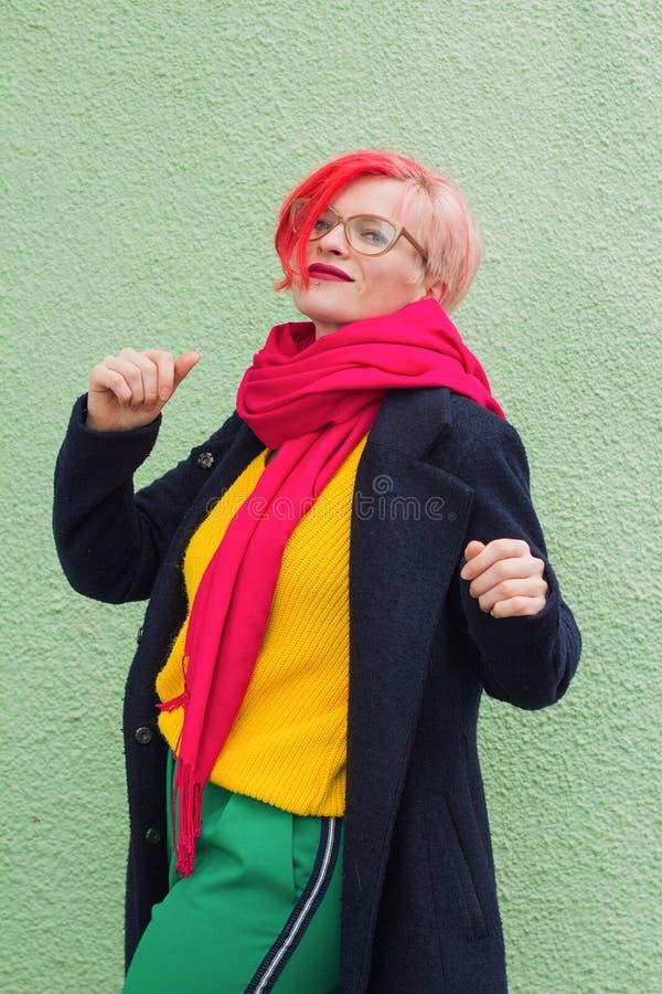 De mooie jonge vrouw met multicolored haar kleedde zich in heldere gekleurde kleren die op groene muurachtergrond stellen stock fotografie