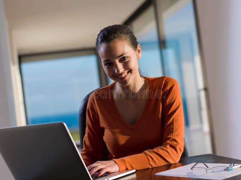 De mooie jonge vrouw ontspant en werkt aan laptop royalty-vrije stock fotografie