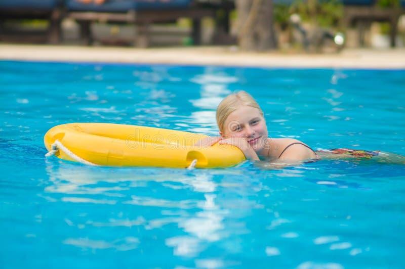 De mooie jonge vrouw ontspant op het levensring in pool in tropische bea royalty-vrije stock foto
