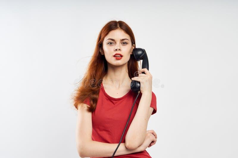 De mooie jonge vrouw op een witte achtergrond houdt een vaste telefoon, mededeling stock foto