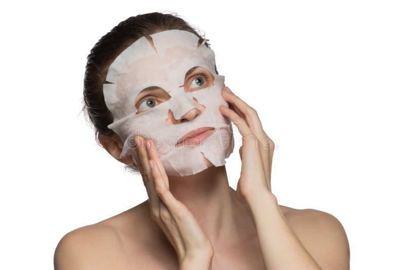 De mooie jonge vrouw past een kosmetisch masker op een gezicht op a toe stock afbeelding