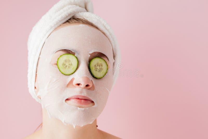 De mooie jonge vrouw past een kosmetisch weefselmasker op een gezicht met komkommer op een roze achtergrond toe stock afbeeldingen