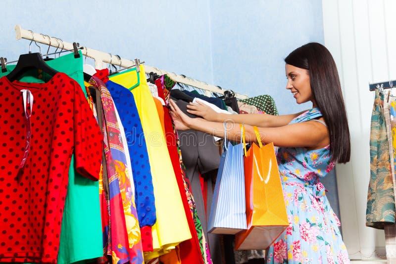 De mooie jonge vrouw probeert om kleren in winkel te vinden stock foto