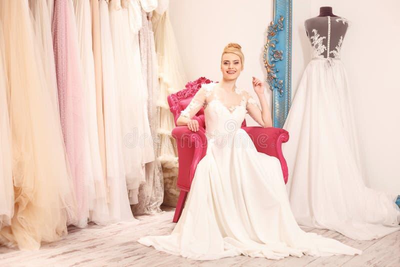 De mooie jonge vrouw probeert op huwelijkskleding royalty-vrije stock afbeelding