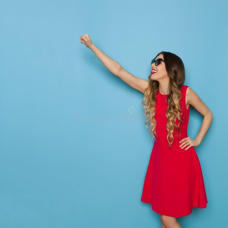 De mooie Jonge Vrouw in Rode Kleding stelt met Opgeheven Vuist stock afbeelding